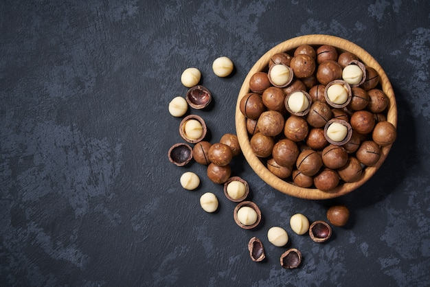 Macadamia nuts in wooden bowl on black with copy space, top view