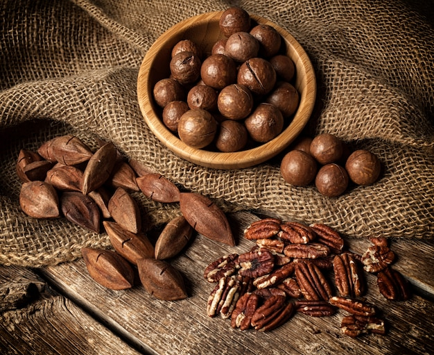 Macadamia, pecan and pili nuts on wooden table