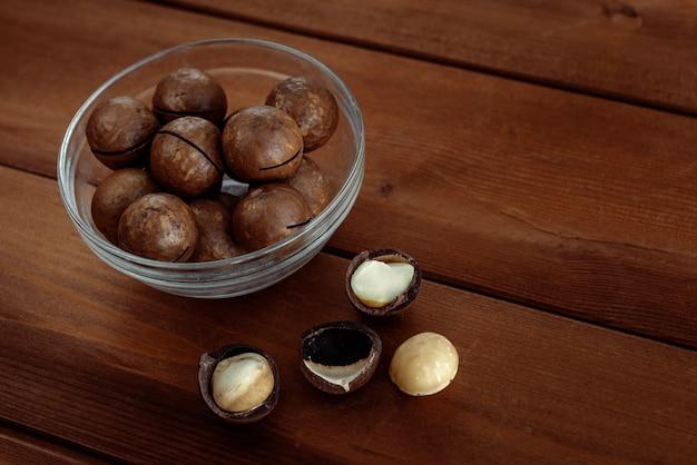 木製のテーブルのボウルにカーネルナッツと一言で言えばマカダミア