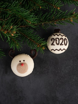 Macaron red nose reindeer and macaron with 2020 number with fir tree brances on dark black background. christmas and new year card