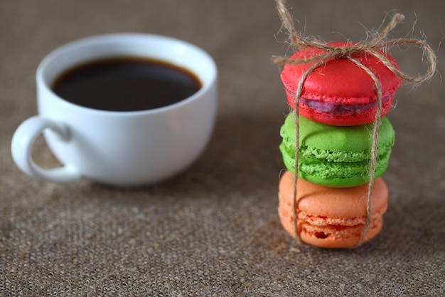 Macaron three pieces red, green and orange tied with rope and a mug of coffee on burlap tablecloth.