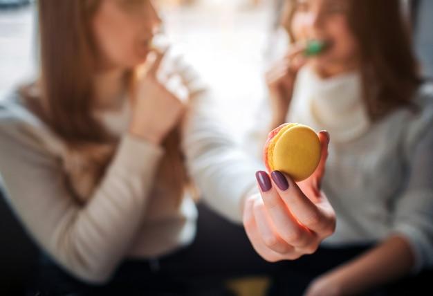 Закройте вверх руки держа желтое macaron в руке. молодые женщины едят куки и смотрят друг на друга. они сидят внутри вместе.