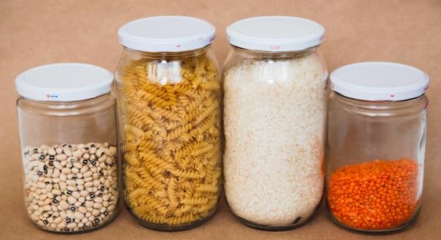 Макароны и бобы в банках на коричневом пространстве. концепция питания. концепция здорового питания.