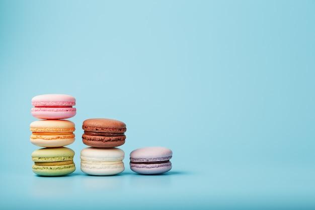 さまざまな色のマカロニクッキーが青色の背景にピラミッド型の階段状に配置されています。