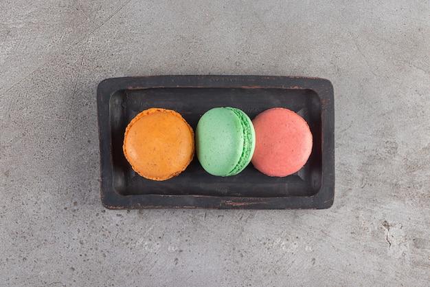 Макаронное печенье разных цветов на темной деревянной доске.
