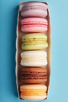 파란색 배경에 흰색 상자에 서로 다른 색상의 마 카로 니 쿠키.