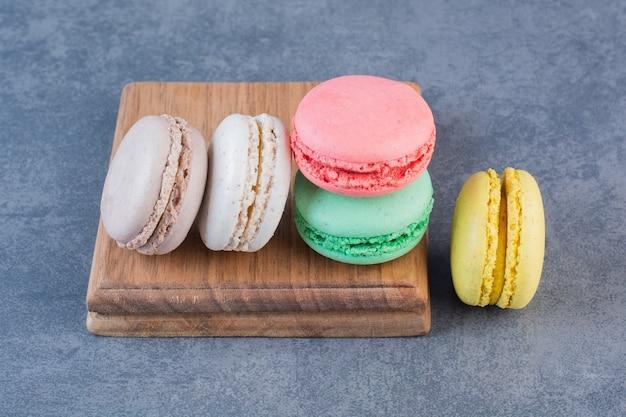 Макаронное печенье разного цвета на темно-серой поверхности
