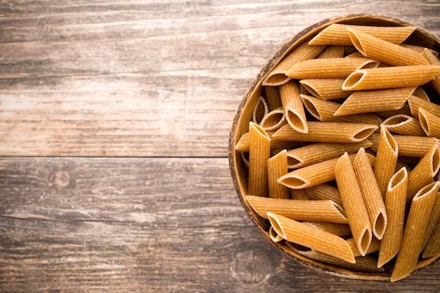 Макароны на миске, деревянном фоне.