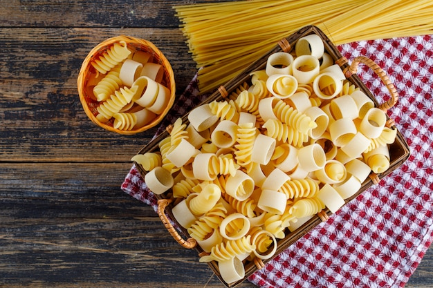 Macaroni pasta in a basket and bucket with spaghetti top view on a picnic cloth and wooden background