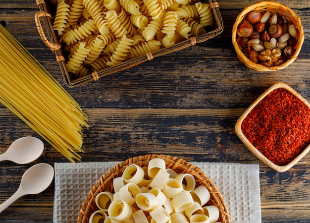 Macaroni pasta in a basket with spaghetti, spoons, various nuts top view on a wooden background space for text