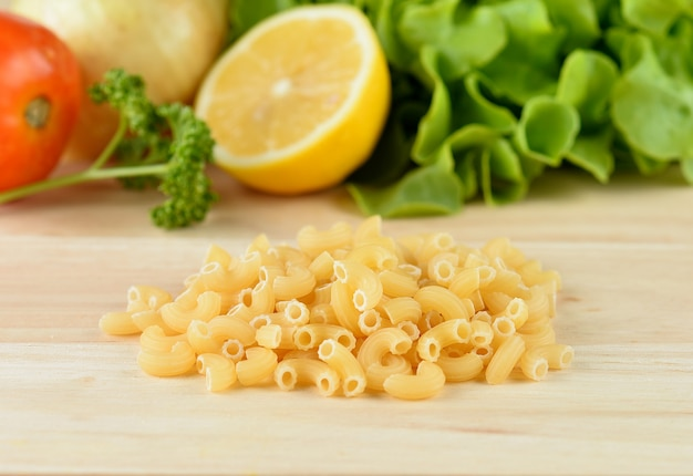 Macaroni pasta close up  on wooden table
