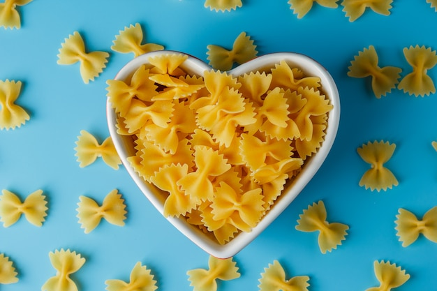 Macaroni pasta in a heart shaped bowl and around on a cyan surface