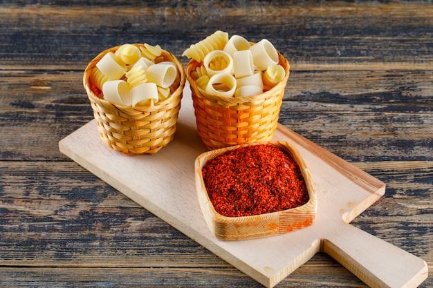 Макаронные изделия макарон в ведрах с красной специей на разделочной доске и деревянной предпосылке. горизонтальный
