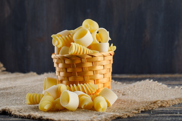Macaroni pasta in a small bucket on sackcloth and dark background, side view. space for text