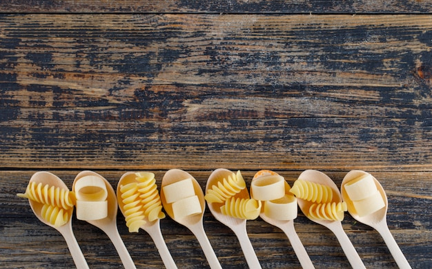 Macaroni pasta in a spoons flat lay on a wooden background free space for your text