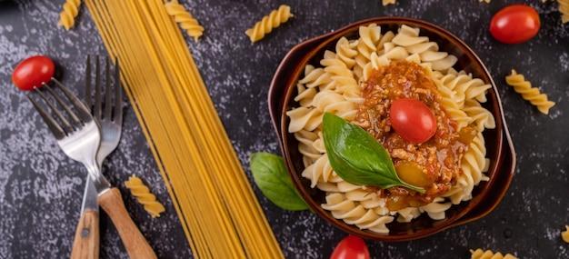 Макароны, обжаренные с помидорами и базиликом на серой тарелке.