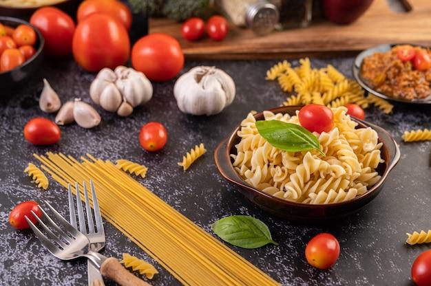 Maccheroni saltati con pomodori e basilico su un piatto grigio.