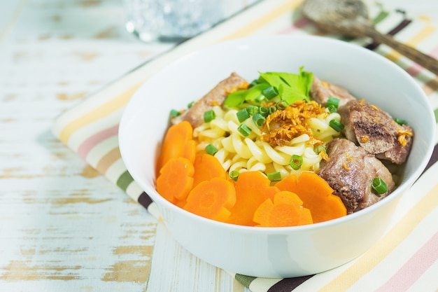 Macaroni soup with pork and carrot on white wooden table