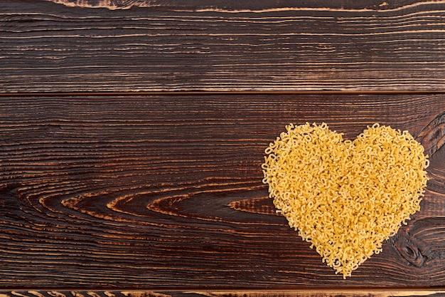 マカロニステリンハート、上面図。木製の背景、コピースペースに生の食品からの心。バレンタインデーの装飾。