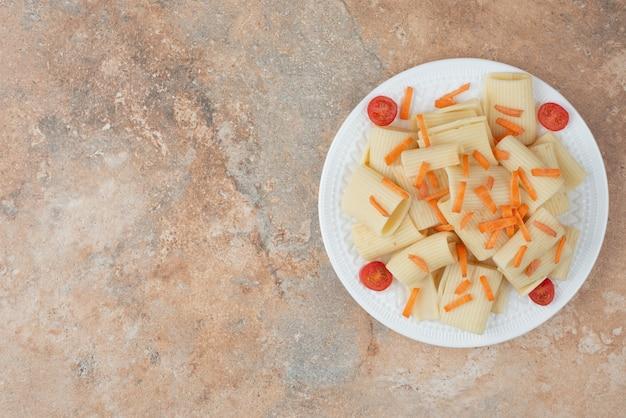 白いプレートにニンジンとトマトチェリーのマカロニ。