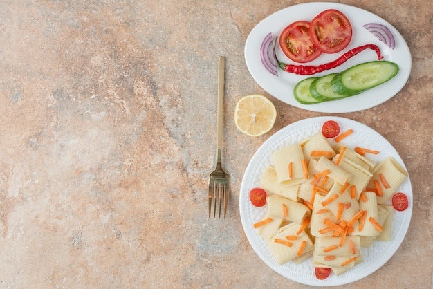 Macaroni with carrot, tomato cherry, cucumber and slice of lemon on white plate