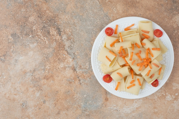 Macaroni with carrot and tomato cherry on white plate