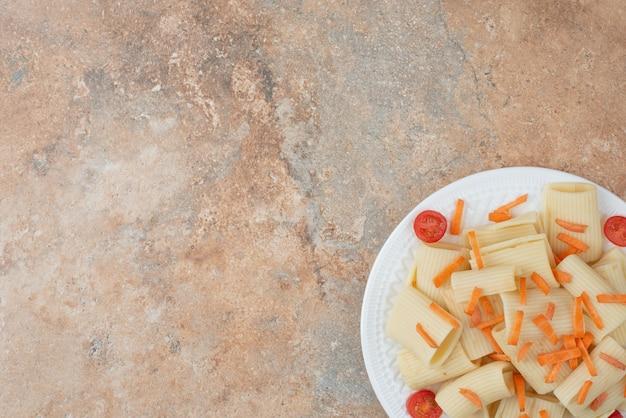Maccheroni con carote e pomodorini sul piatto bianco.