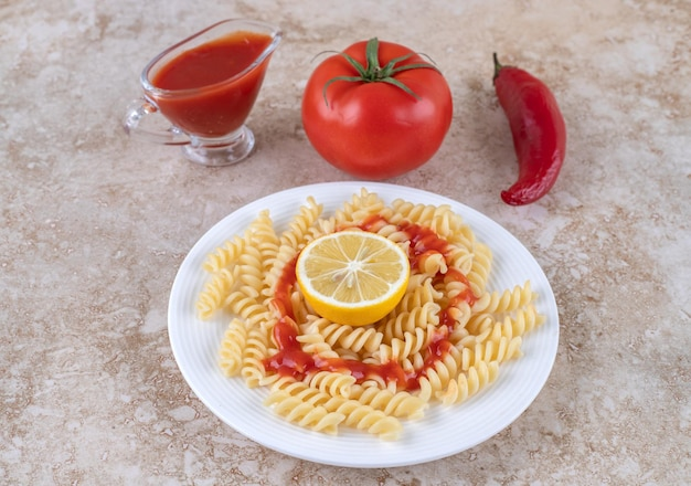 Macaroni with a glass of ketchup and various vegetables on marble surface.