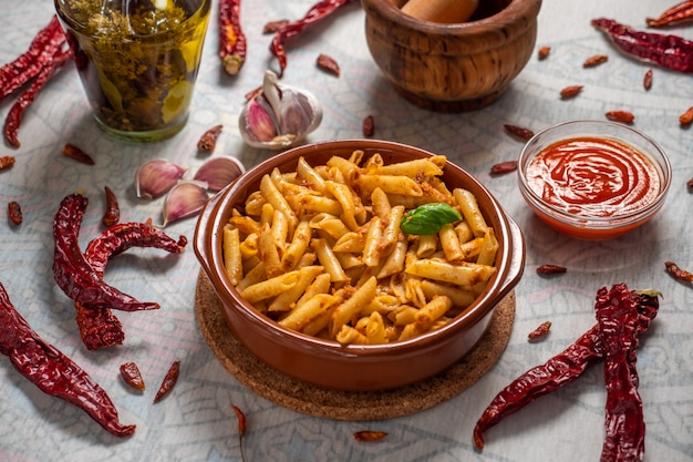 Macaroni with red pesto in a clay pan and some ingredients around