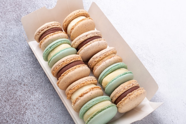 Macarons in box on stone background. delicious french macarons. copy space, top view - image Premium Photo