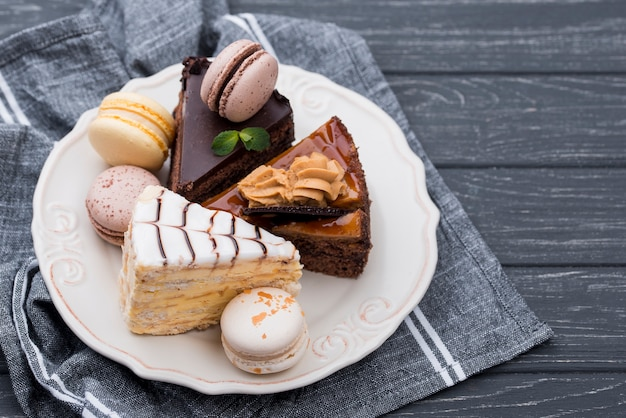Macarons and cakes on plate with mint