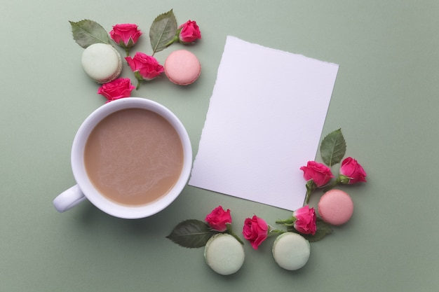 Macarons, coffee and rose on green background. top view. flat lay