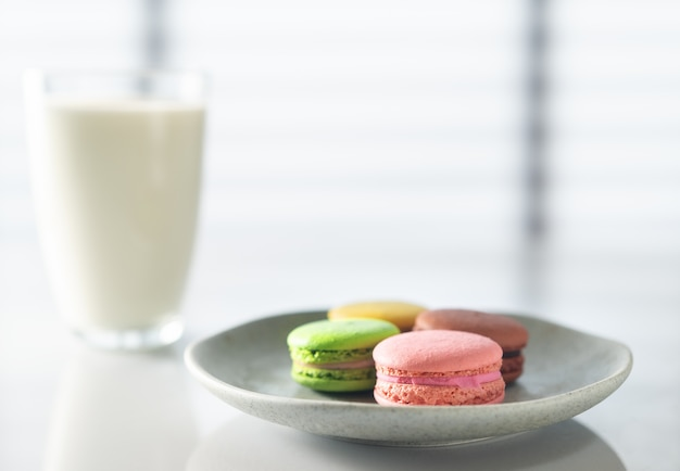 Macarons  cookies and milk on the kitchen table