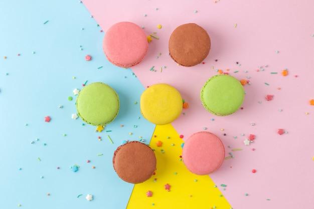 マカロン。フランスの色とりどりのマカロンケーキ。明るいマルチカラーの背景に小さなフランスの甘いケーキ。デザート。お菓子。上面図