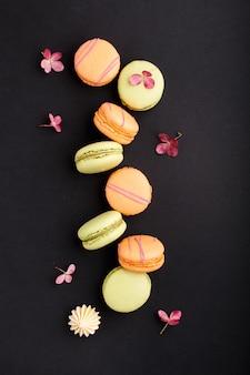 Оранжевые и зеленые macarons или торты macaroons на черной поверхности, взгляд сверху, конце вверх.