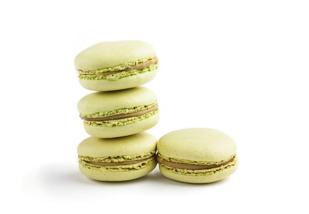 Зеленые торты macarons или macaroons изолированные на белой предпосылке, взгляде со стороны.