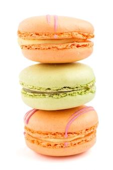 Оранжевые и зеленые macarons или торты macaroons изолированные на белой предпосылке, взгляде со стороны.