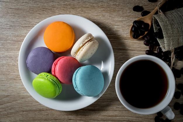 カップの黒いコーヒーと木製のテーブルの背景にコーヒー豆と白い皿の上のマカロン