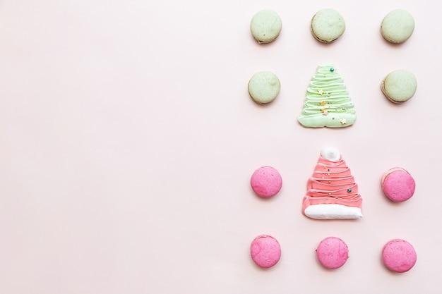 淡いピンクのテーブルのお菓子の背景にマカロンピンクと緑。