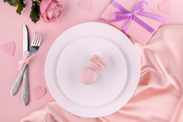 Macarons on plate with cutlery and gift