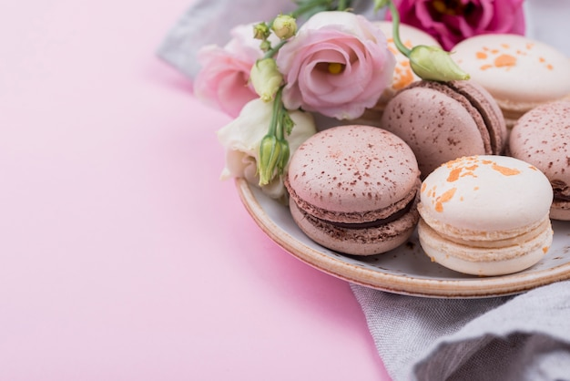 Macarons on plate with roses and copy space