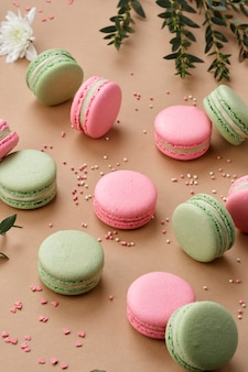 Macarons surprisingly tender green and pink colors neatly laid out on a beige background