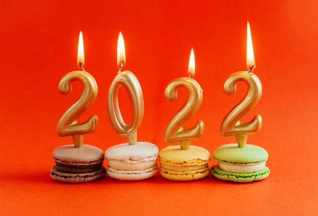 Macarons с зажженными свечами 2022 на красном фоне. новый год.
