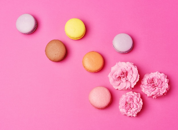 Macarons with cream and a pink rose bud with scattered petals background