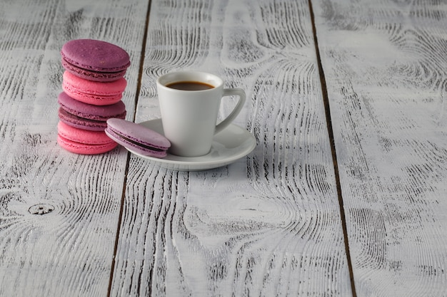 Macarons с чашкой кофе на деревянный стол
