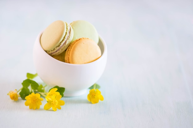 Macarons wooden table and beauty flowers