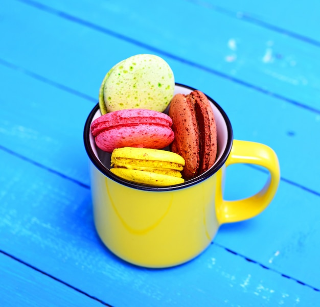 Macarons in a yellow ceramic cup