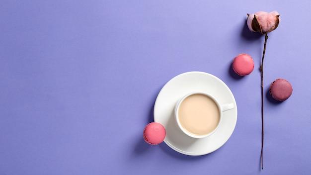 Белая чашка кофе с молоком и вкусные macarons, цветок хлопка на нежном фоне сирени. вид сверху, копия пространства. весенняя открытка, обои