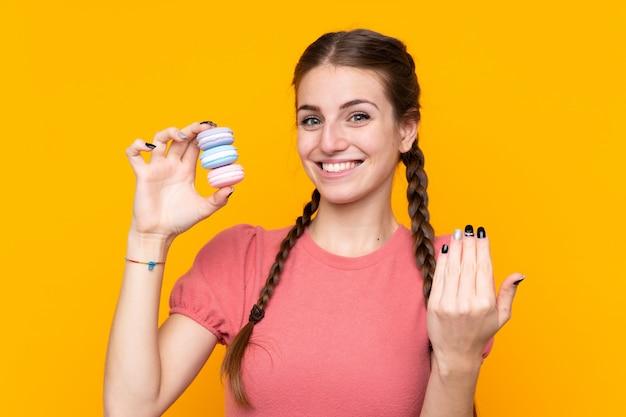 Молодая женщина над изолированной желтой стеной держит красочные французские macarons и приглашает прийти