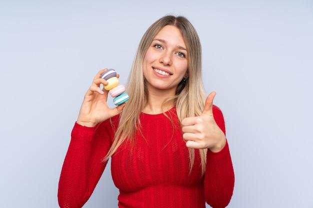 Молодая белокурая женщина над изолированной голубой стеной держа красочные французские macarons с большими пальцами руки вверх